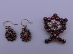 A garnet and seed pearl brooch and a pair of garnet set earrings. The former 2.5 cm high.