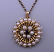 A 9 ct gold seed pearl and garnet pendant on a chain. 2.25 cm diameter. 9.9 grammes total weight.