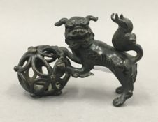 A Chinese patinated bronze model of a dog-of-fo and ball. 11.5 cm long.