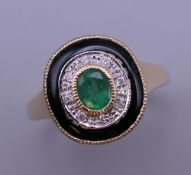 An Art Deco style 9 ct gold emerald, diamond and onyx ring. Ring size O/P. 3.8 grammes total weight.