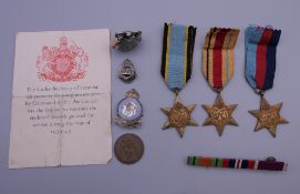 A small quantity of militaria, including three WWII medals, a lighter, badges, etc.