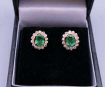 A pair of 18 ct gold emerald and diamond earrings. 1 cm high.