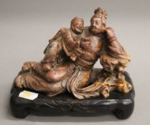 A Chinese soapstone carving on a wooden base. 13 cm high.