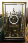 A brass skeleton clock, under glass case. 54 cm high overall, 33.5 cm wide, 23.5 cm deep.