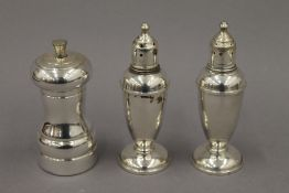 A sterling silver peppermill and a pair of weighted sterling silver salt and pepper pots. 14.