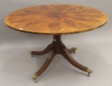 A circular cross banded mahogany centre table. 131 cm diameter.