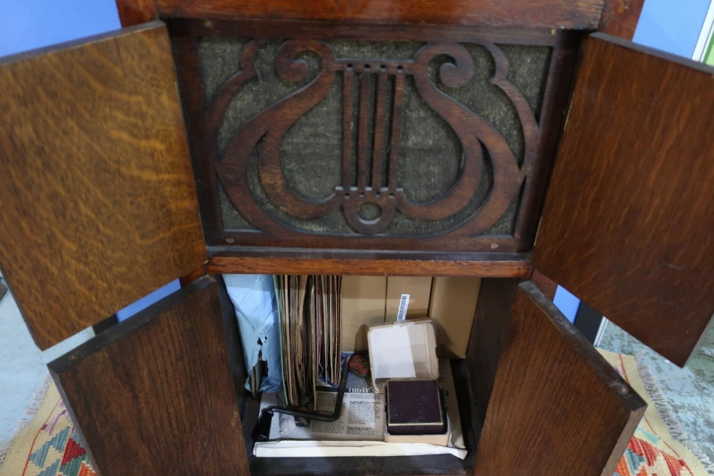 Lot 460 - Early 20th C oak cased gramophone with hinged top and four cupboard doors, with various records