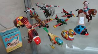 Friction powered tin plate aeroplanes and helicopters, a boxed clockwork sparrow, donkey boy and