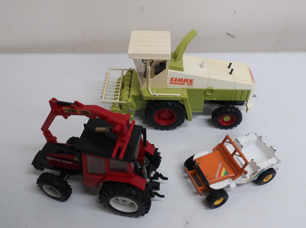 Britains die-cast model of a green tractor, flatbed trailer, another tractor, plastic Claas Jaguar