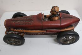 Cast resin model of a vintage single seater racing car with red body on black spoked wheels (L50cm)