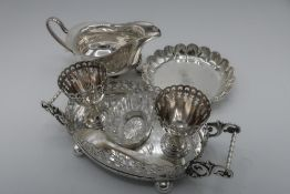 Edwardian EPNS two cup oval egg cruet with pierced borders, scroll handles and ball feet (L.19cm),