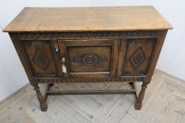 17th C style oak low side cabinet, with overhanging top, and scroll carved frieze above two