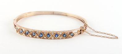 An unmarked yellow gold sapphire & diamond hinged bangle, the nine sapphires weighing a total of