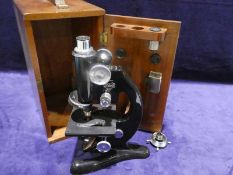 A Beck of London 20th century Microscope number 26142, black enamelled, in fitted mahogany case