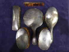 Six items of silver backed Dressing Table Ware, four brushes, hand mirror and comb, all bumped