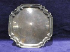 A mid 20th century silver four footed Salver, square with canted corners, raised rim on shallow ball