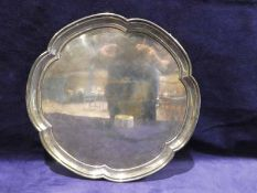 A mid 20th century silver three footed tray, shaped circular form with raised rim, Sheffield 1957,