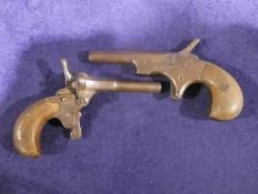 Two small 19th century Pocket or Muff Pistols, single barrel percussion action wooden grips
