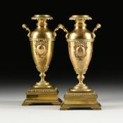 A PAIR OF VICTORIAN TWO HANDLED POLISHED BRASS VASES, 19TH CENTURY, each with a circular leaf tip