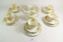 A Sutherland tea service comprising: five cups and saucers, five tea plates , cake plate , milk