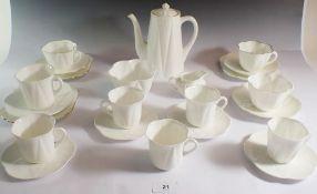 A Shelley white group of tea and coffee ware consisting of coffee pot, three tea plates, three tea
