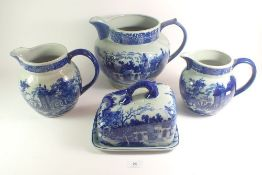 Three large blue and white pottery jugs plus a cheese/butter dish