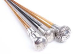 Two tapered walking canes with decorative silver pommels, together with one similar