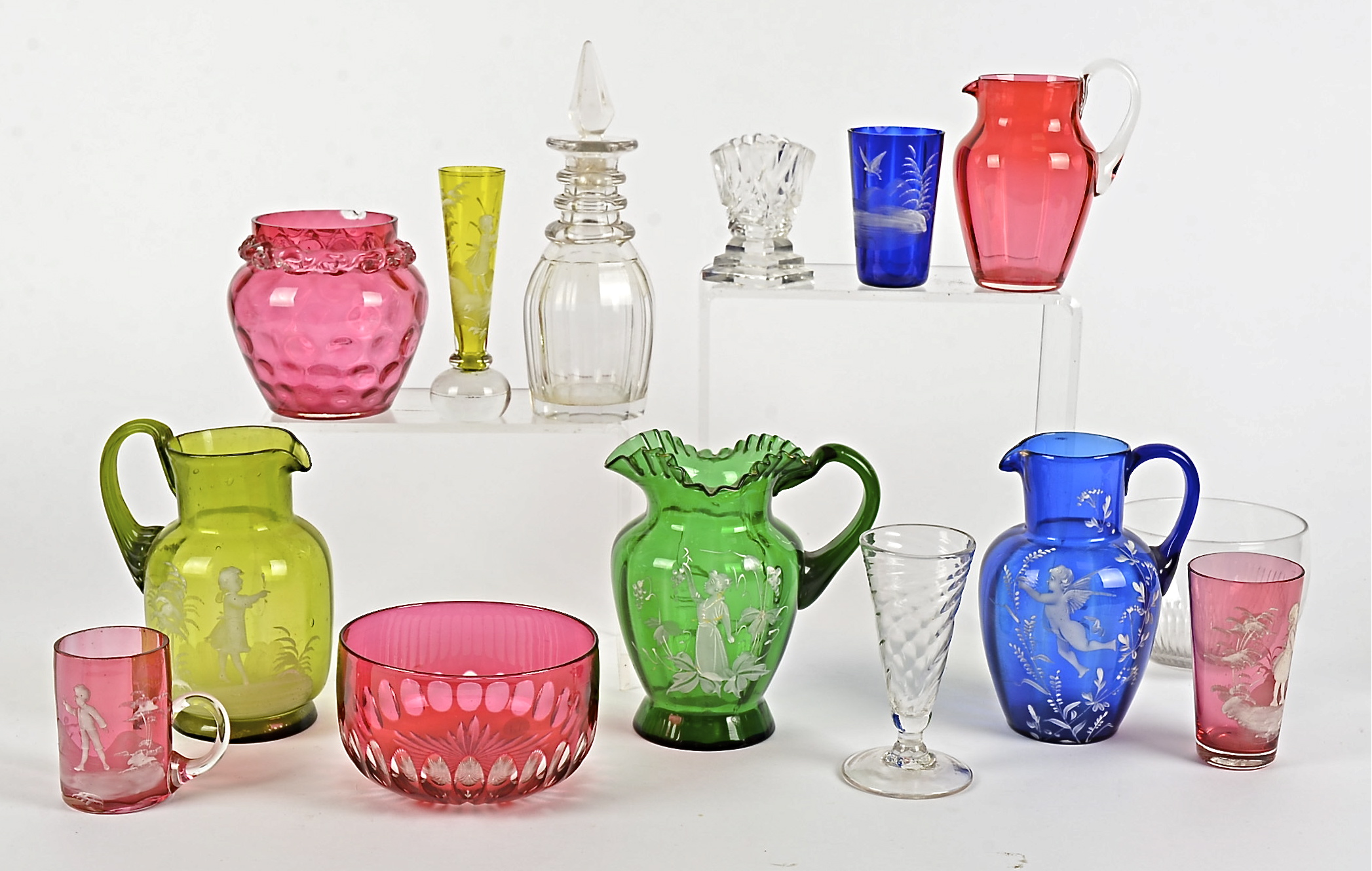 Lot 207 - Three Mary Gregory 19th and 20th Century glass jugs, one blue example with a putti, one with a