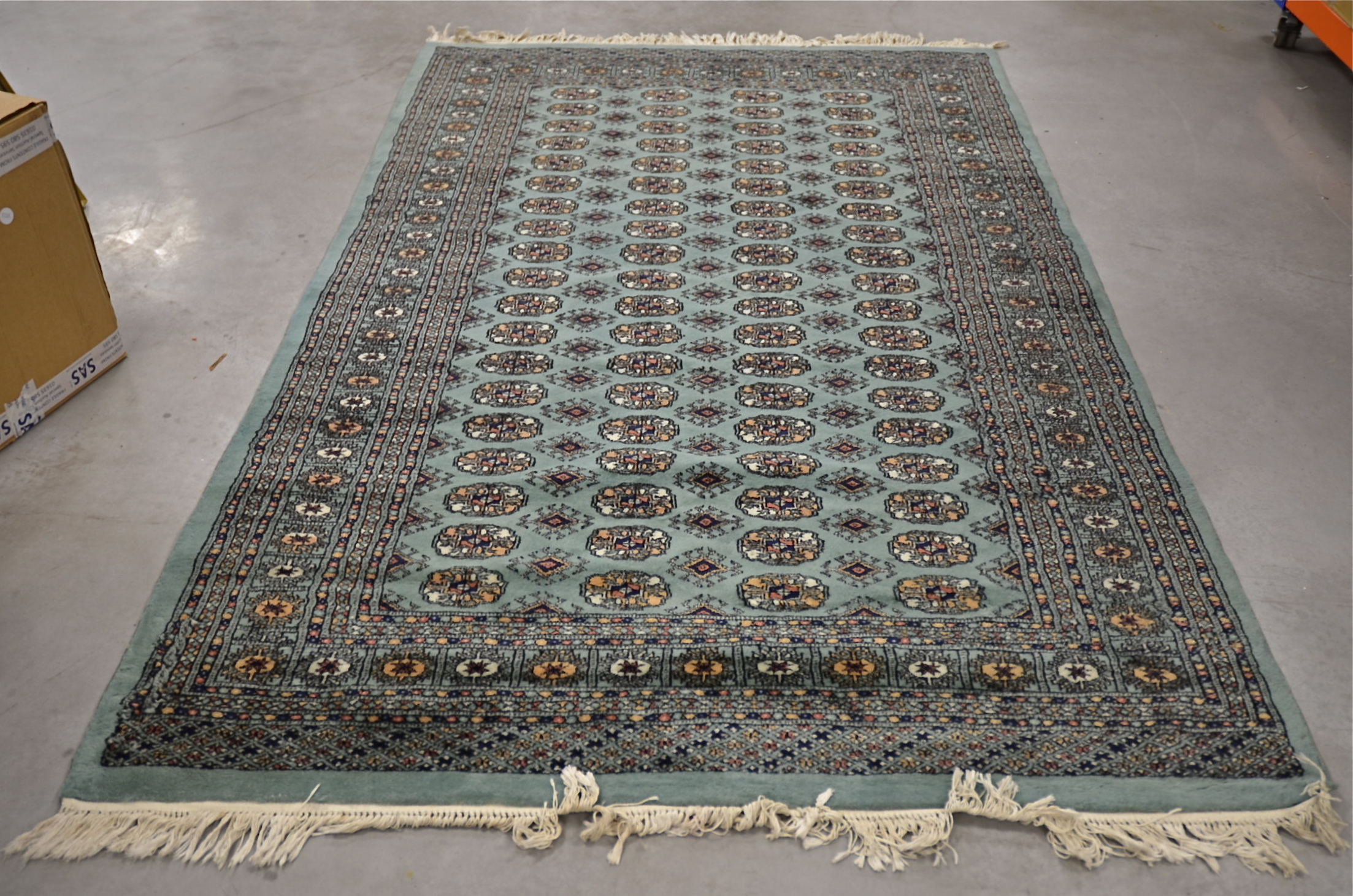 Lot 585 - A Middle Eastern 20th Century woollen rug, with a sequential geometric pattern to the central panel,