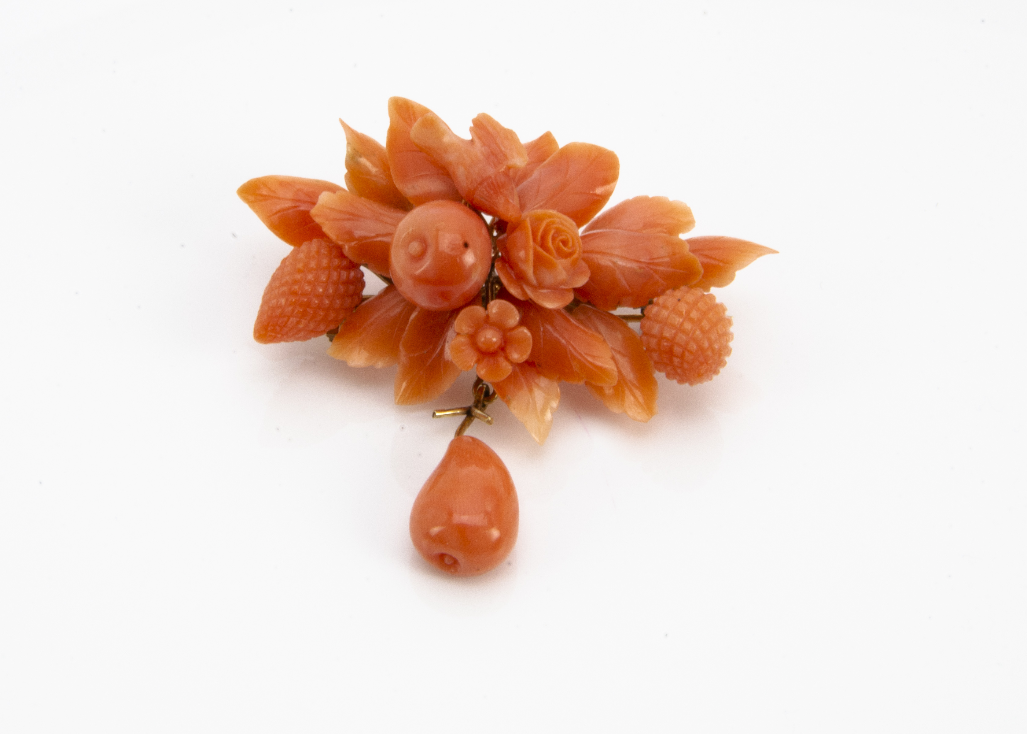 Lot 256 - A 19th Century Italian coral brooch, the floral and fruit carved coral surmounted by a small