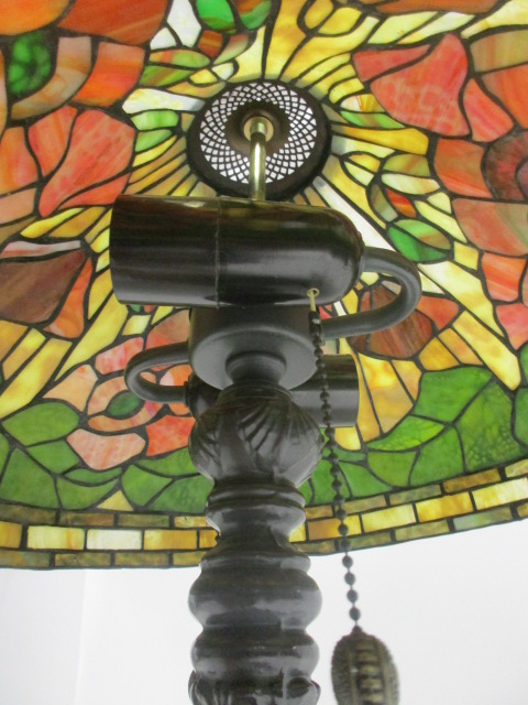 Lot 124 - A Tiffany style lamp, decorated in poppies, on a cast metal base, height 63cm