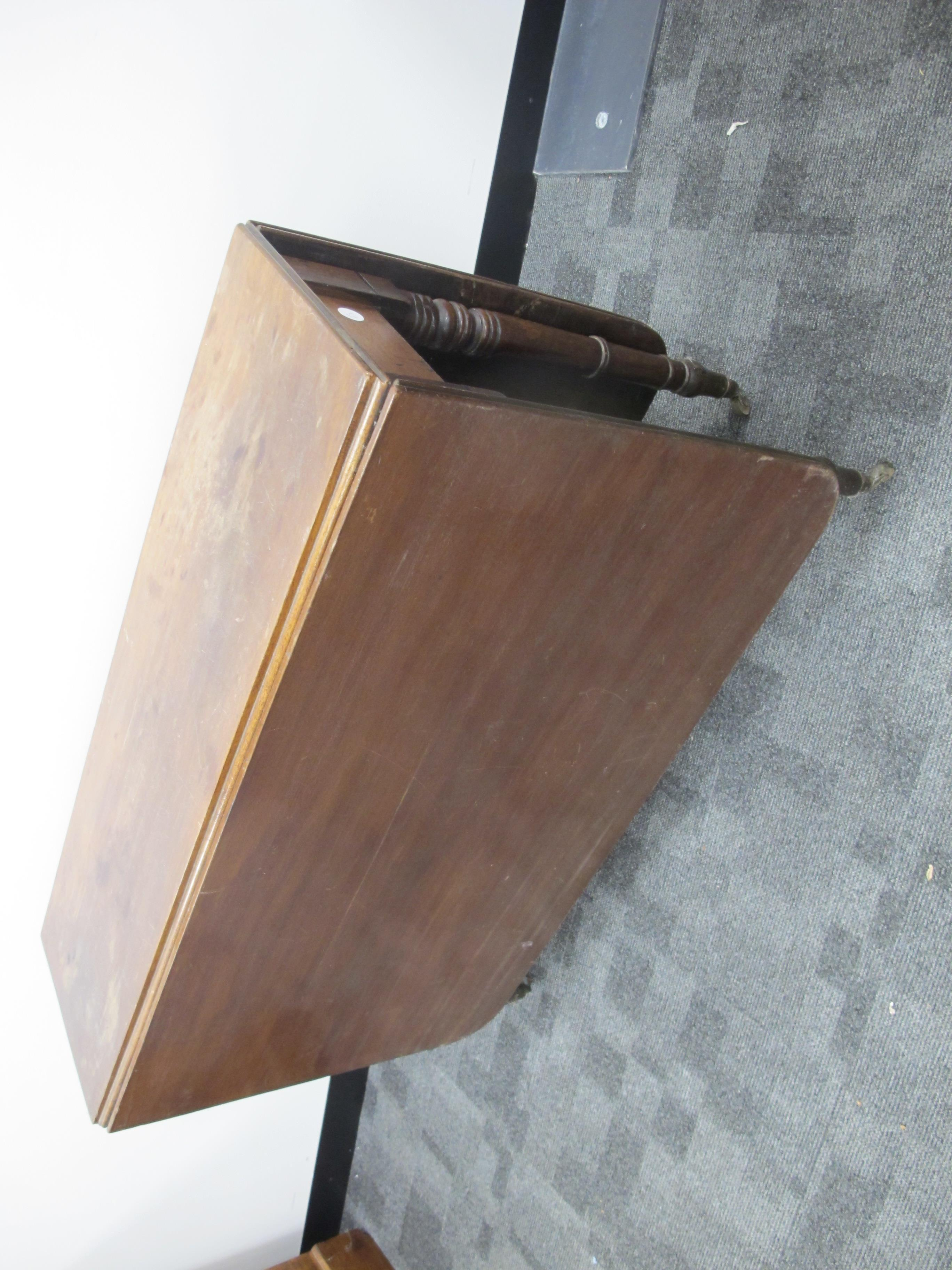 Lot 447 - An antique mahogany drop flap table, rounded corners, raised on turned supports, finished on brass