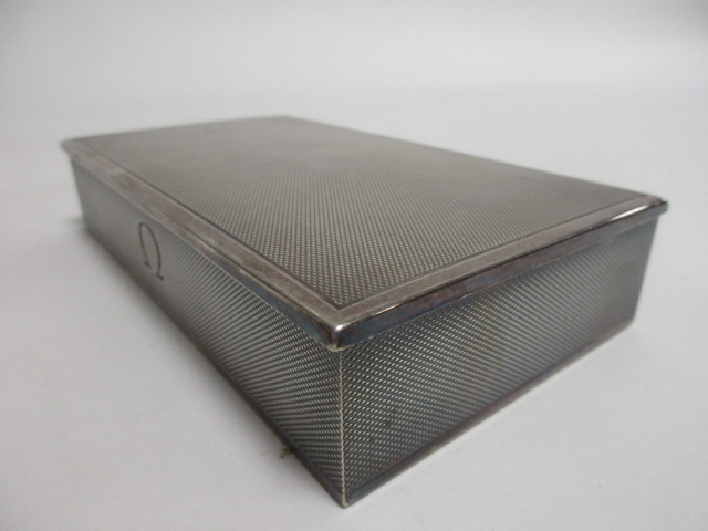 Lot 1 - A 1960s Omega sterling silver presentation box, with engine turned decoration and a wooden lined