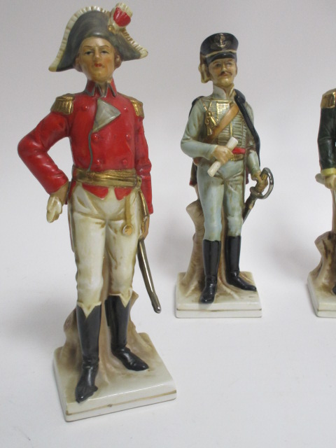 Lot 60 - Three 20th Century porcelain soldiers, together with a continental figure of a lady in the Edwardian