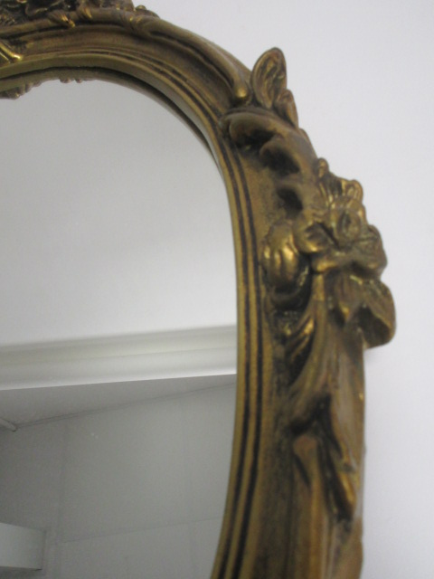 Lot 85 - A giltwood framed oval mirror in the rococo style, length 66cm
