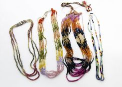 A collection of multi strand corundum bead necklaces, in various colours ranging from rubies,