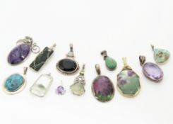 A collection of hardstone pendants, including three turquoise set in silver, an amethyst matrix in