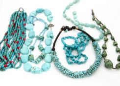 Six various turquoise necklaces, including a multi strand with coral spacers, another large pebble
