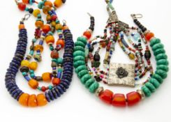 A collection of North African and Middle Eastern coloured bead necklaces, including a white metal