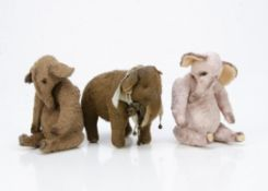 Three artist made elephants, of artificial silk plush, a pink elephant with swivel head and