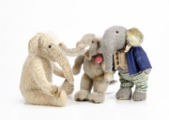 Two artist made elephants, a grey plush jointed elephant with checked trousers and blue jacket --11