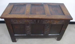 An antique oak three panelled coffer with carved frieze, some later alterations including a