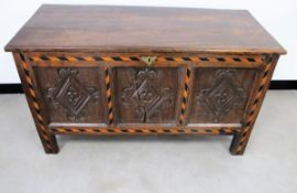 An antique oak panelled coffer, hinged plank top, the front having diamond shape carvings to