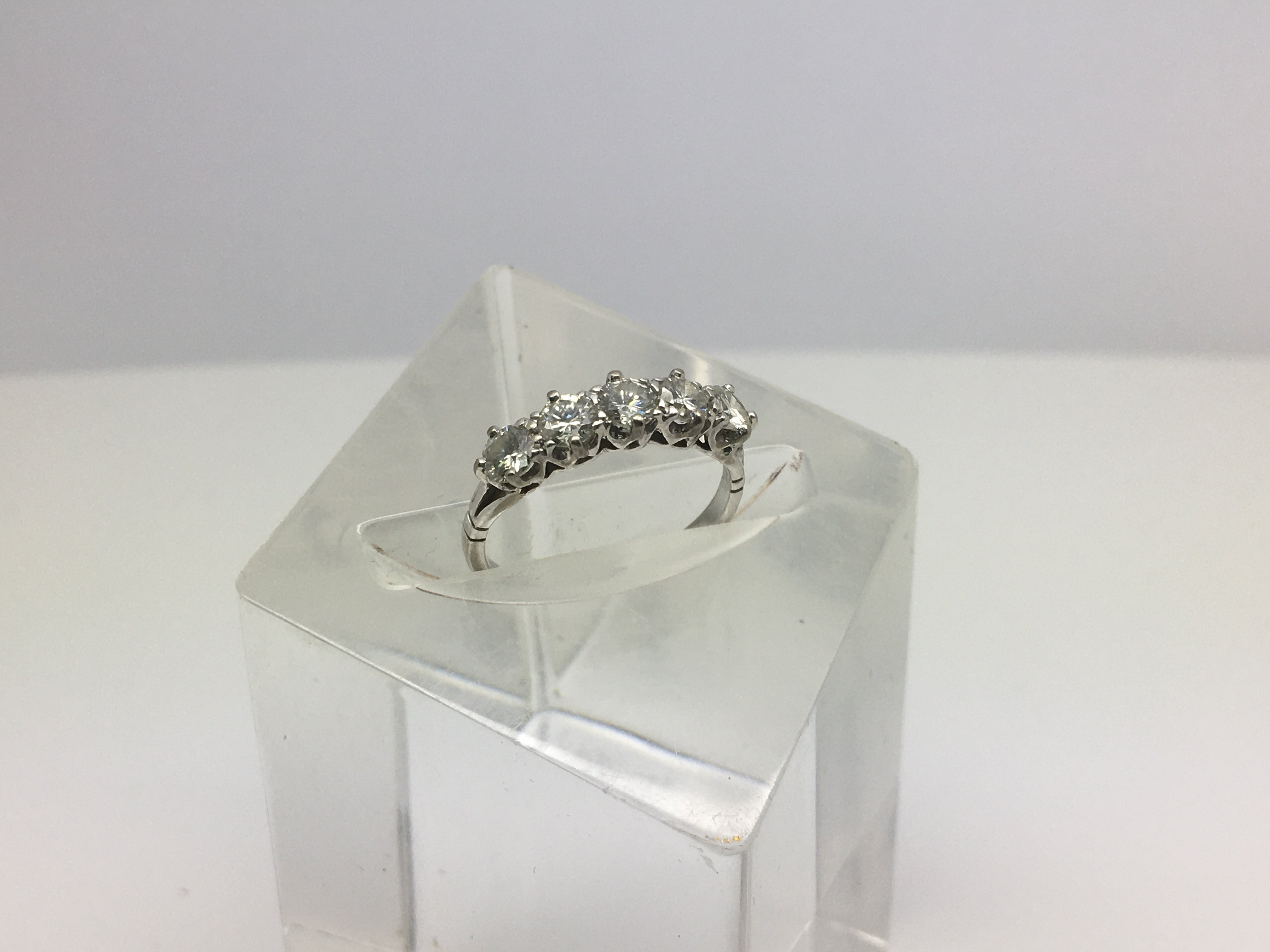 Lot 11 - A white metal ring, possibly platinum, with a row