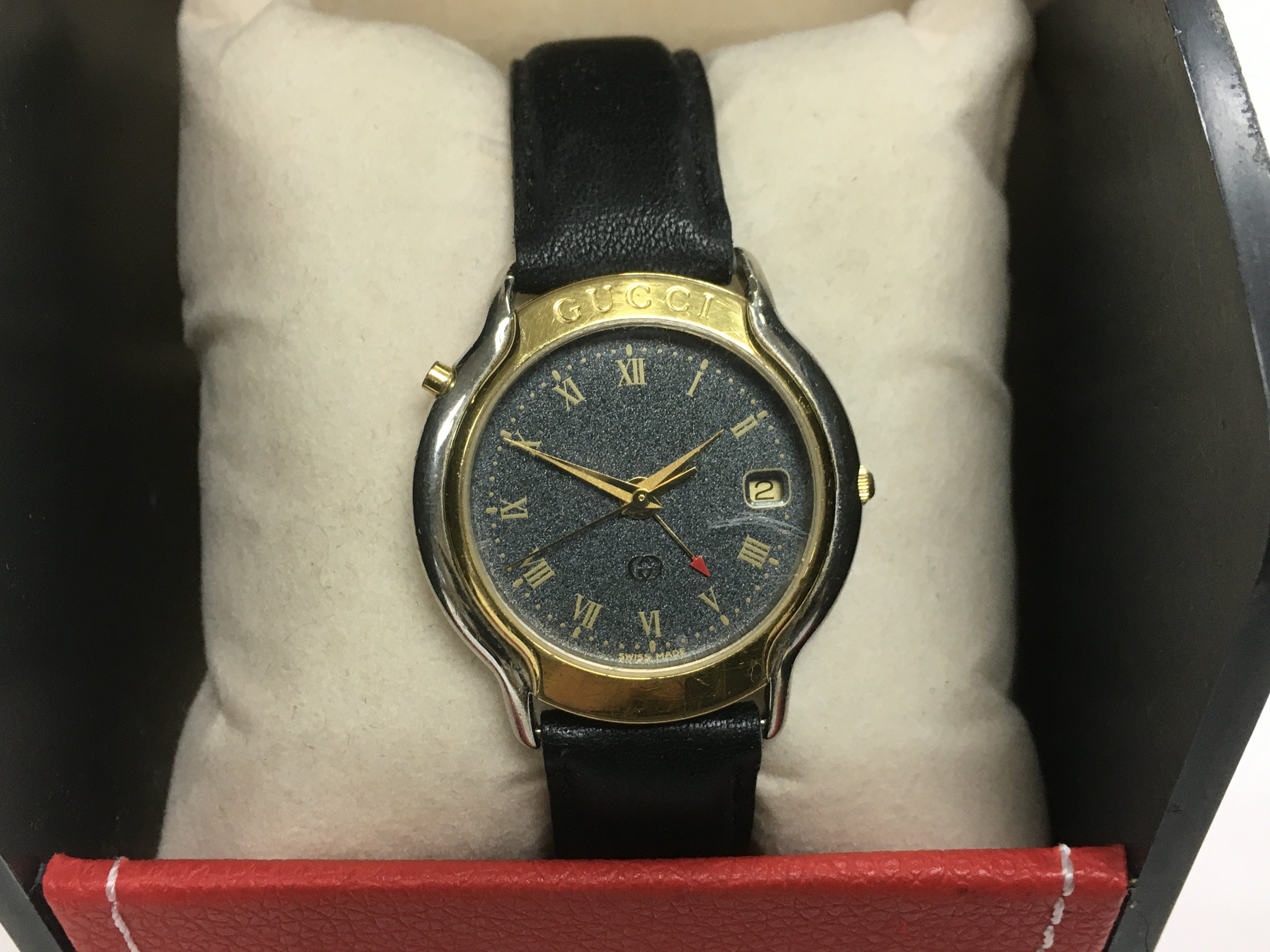 Lot 57 - A Gucci black and gold tone watch with a black lea