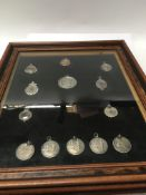 A collection of silver sporting medallions in a oa