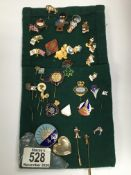 A collection of various pin badges including Golde