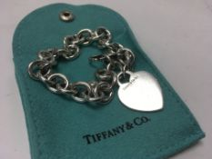 A Tiffany and Co. silver heart bracelet.
