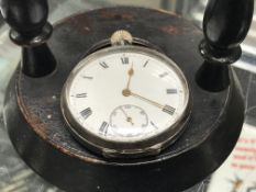 A hallmarked silver pocket watch and turned wooden pocket watch stand