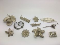 Eleven silver brooches, various designs.